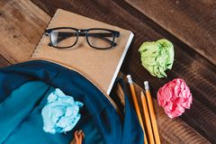 Szkolna torba, eyeglasses, ołówek, notatnik i kolorowy zawijający papier na drewnianym stole, fotografia stock