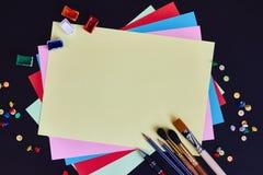 Szkolne dostawy i pusty prześcieradło z kopii przestrzenią dla teksta barwiony papier na czarnym tle Obrazy Royalty Free