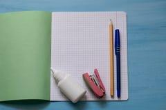 Szkolne dostawy na notatnika prześcieradle Szkolny pojęcie z materiały Szkolny notatnik, kleidło, zszywacz, ołówek i pióro, Uczeń zdjęcia stock