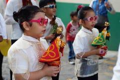Szkolne dziewczyny paradują ulicznego tana w kolorowych kostiumach, przewożenie niemowlaka Jezus ikona Zdjęcie Stock