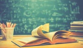Szkolne książki na biurko formułach i Physics inskrypcja na bla fotografia stock