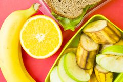 Szkolnego lunchu pudełko Chleb, pomarańcze, dziecko kukurudze, marchewka i pomidory w zielonym plastikowym zbiorniku, zdjęcie royalty free