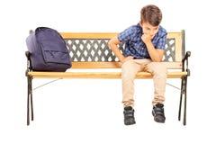 Szkolnej chłopiec obsiadanie na główkowaniu i ławce zdjęcia stock