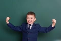 Szkolnej chłopiec przedstawienia bicepsów mięśnie, portreta chalkboard pobliski zielony pusty tło, ubierali w klasycznym czarnym  Zdjęcia Royalty Free