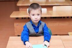Szkolnej chłopiec obsiadanie w sala lekcyjnej Zdjęcie Stock