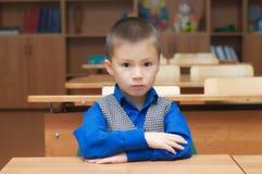 Szkolnej chłopiec obsiadanie w sala lekcyjnej Obraz Stock