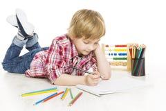 Szkolnej chłopiec writing ćwiczenie w notatniku Uczeń robi pracie domowej Obrazy Royalty Free