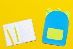 Szkolnej torby plecak, notatniki i ołówki, tapetujemy cięcie na żółtym tle Zdjęcie Royalty Free