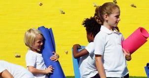 Szkolni dzieciaki trzyma joga matę i oddziała wzajemnie z each inny zdjęcie wideo
