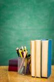 Szkolni podręczniki na biurku przed blackboard Zdjęcie Stock