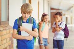 Szkolni przyjaciele znęcać się smutnej chłopiec w korytarzu zdjęcia stock