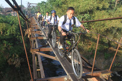 Szkolni ucznie iść szkoła przez zawieszenie mosta zdjęcie royalty free
