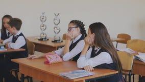Szkolni ucznie siedzą smutnego w sali lekcyjnej zbiory wideo
