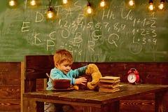 Szkolny bufet Chłopiec w szkolnym bufecie Szkolny bufet dla zdrowego łasowania Dziecko karmy misia zabawka wewnątrz zdjęcia royalty free