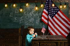 Szkolny dzieciak przy lekcją w 4th Lipiec Nauczanie online lub online kursy uczy kogoś w domu Patriotyzm i wolność mały chłopiec zdjęcie stock