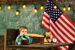 Szkolny dzieciak przy lekcją w 4th Lipiec Szczęśliwy dzień niepodległości usa Patriotyzm i wolność Chłopiec je chleb przy obrazy royalty free