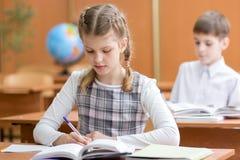Szkolny dziewczyny writing w notatniku w sala lekcyjnej obraz royalty free
