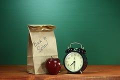 Szkolny lunch, Apple i zegar na biurku przy szkołą, Obrazy Royalty Free