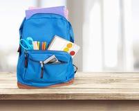 Szkolny plecak z materiały na drewnianym zdjęcie stock