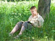 Szkolny uczeń czyta książkę w parku Fotografia Royalty Free