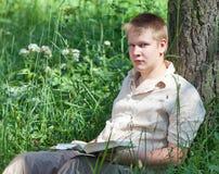 Szkolny uczeń czyta książkę w parku. Portret Obrazy Royalty Free