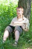 Szkolny uczeń czyta książkę w parku na trawie Obraz Royalty Free
