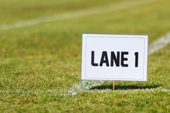Szkolny zawody atletyczni pasa ruchu 1 znak na trawie Fotografia Royalty Free