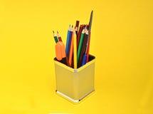 Szkolnych dostaw rzecz w pudełku na Żółtym tle Zdjęcia Stock