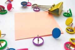 Szkolnych i biurowych dostaw papierowe klamerki, szpilki, notatki, majchery na białym tle obraz royalty free