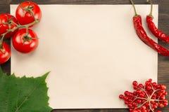 Szkotowy rocznika papier z jagodami, pomidorami, chili pieprzem i winogronem, opuszcza na drewnianym tle zdrowe jedzenie wegetari obraz stock