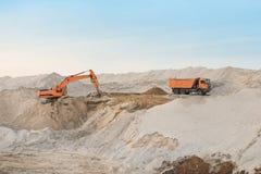 Szlakowa ekskawatoru ładowania ziemia na ciężarówce przed chmurnym niebem Zdjęcia Stock