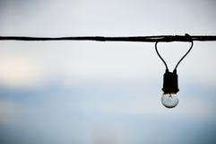 Sznurek depeszujący żarówka na niebieskiego nieba tle Obraz Royalty Free
