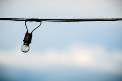 Sznurek depeszujący żarówka na niebieskiego nieba tle Fotografia Stock