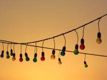 Sznurek Multicoloured żarówki przy zmierzchem Fotografia Stock