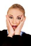 Szokować biznesowej kobiety mienia ręki na policzkach Zdjęcie Royalty Free