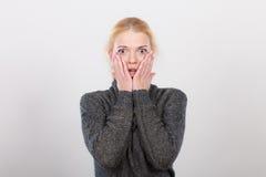 Szokować kobiety mienia ręki na twarzy Obrazy Stock