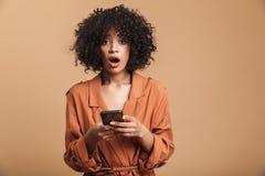 Szokująca ładna afrykańska kobieta używa smartphone i patrzejący kamerę obraz royalty free