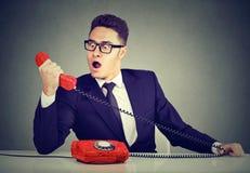 Szokująca biznesowego mężczyzna odbiorcza zła wiadomość na telefonu obsiadaniu przy biurkiem w jego biurze Zdjęcia Royalty Free