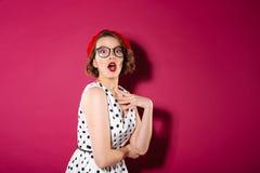 Szokująca imbirowa kobieta patrzeje kamerę w sukni i eyeglasses obrazy stock