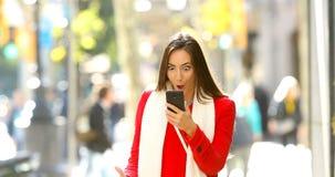 Szokująca kobieta czyta online wiadomość w ulicie