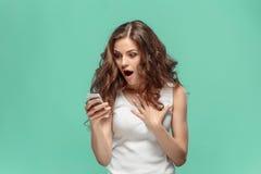 Szokująca kobieta patrzeje telefon komórkowego na zielonym tle fotografia royalty free