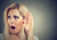 Szokująca kobieta trzyma jej rękę blisko ucho i słucha ostrożnie zdjęcie stock
