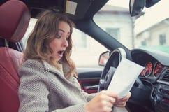 Szokująca kobieta w samochodowym czytelniczym ubezpieczenie papierze obraz royalty free