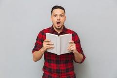 Szokująca mężczyzna mienia książka w rękach Obraz Royalty Free