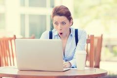 Szokująca młoda biznesowa kobieta używa laptop patrzeje ekran komputerowego Fotografia Stock