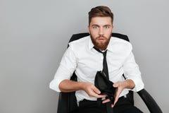 Szokujący brodaty mężczyzna w białego koszulowego seansu pustym portflu Fotografia Stock