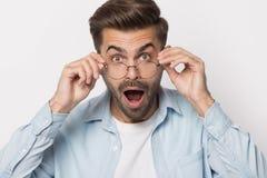 Szokujący facet obniża szkła patrzeje kamery studia strzał obraz stock