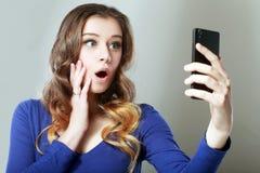 Szokujący kobiety spojrzenie przy telefonem obrazy royalty free