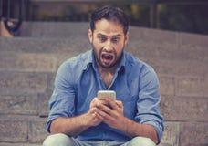 Szokujący mężczyzna patrzeje telefon komórkowego widzii złą wiadomość lub czytelniczą wiadomość tekstową zdjęcia stock