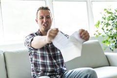 Szokujący mężczyzna trzyma niektóre dokumenty na kanapa pokoju dziennym Obraz Stock